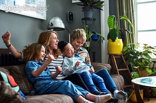 Cheerful family with two mums watching tv at home - gettyimageskorea