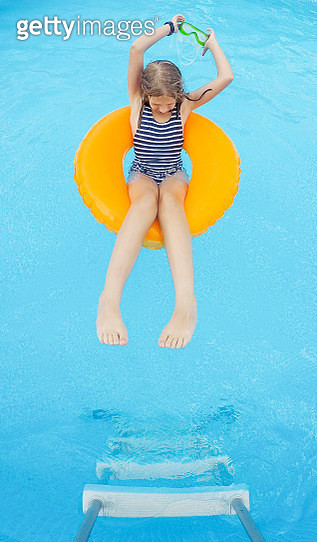 Girl relaxing in backyard pool - gettyimageskorea
