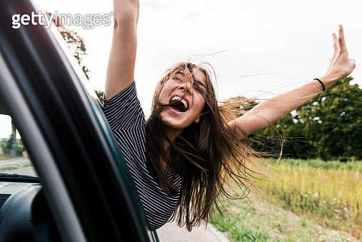Carefree young woman leaning out of car window screaming - gettyimageskorea