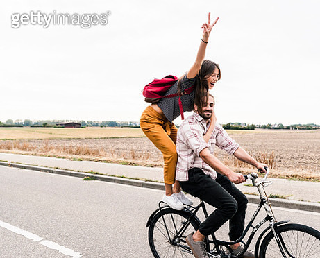 Happy young couple riding together on one bicycle on country road - gettyimageskorea