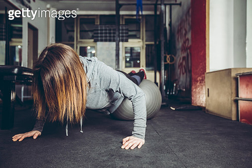Young woman doing push-ups - gettyimageskorea