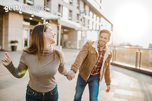 Young couple walking in the city hand in hand and laughing - gettyimageskorea