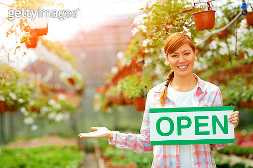 Smiling Florist Holding Open Sign. - gettyimageskorea