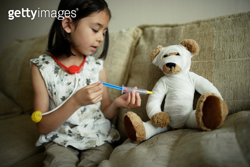 Girl plays doctor doctor giving bandaged teddy an injection with a toy syringe. - gettyimageskorea
