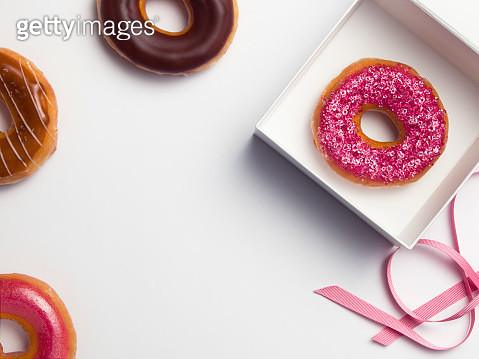 Open white box with pink ribbon containing a diamanté covered pink donut - gettyimageskorea