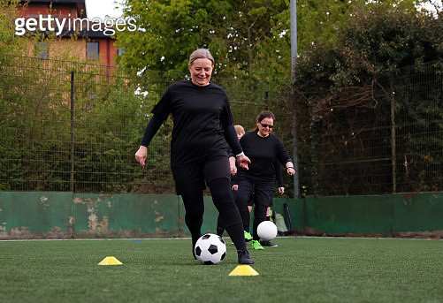 Woman dribbles ball during football practice - gettyimageskorea