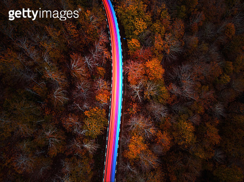 Aerial view of colorful lights moving fast in a mountain road between autumn trees. - gettyimageskorea