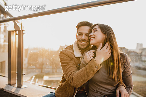 Young couple sitting outdoors and hugging - gettyimageskorea