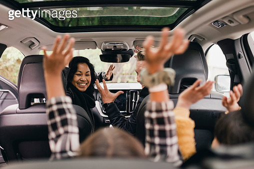 Cheerful family raising hands while enjoying road trip in electric car - gettyimageskorea