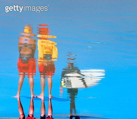 Beach goers reflected in water - gettyimageskorea