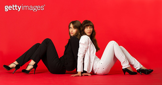 Portrait Of Business People Sitting On Red Background - gettyimageskorea