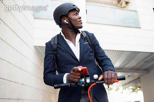 Young businessman with push scooter, smartphone and earphones looking around - gettyimageskorea