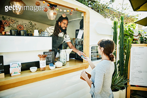 Smiling food truck owner taking credit card for payment from customer - gettyimageskorea