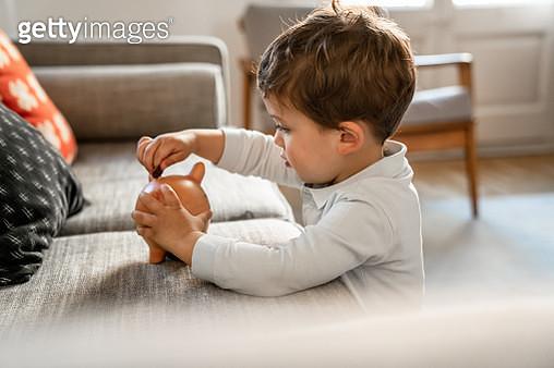 Boy putting coins on piggy bank - gettyimageskorea