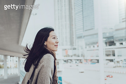 Beautiful young Asian lady overlooking cityscape of Hong Kong on urban bridge - gettyimageskorea