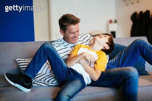 Carefree father and son having fun on couch at home - gettyimageskorea