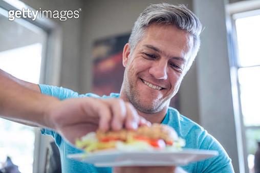 Man having a sandwich from plate - gettyimageskorea
