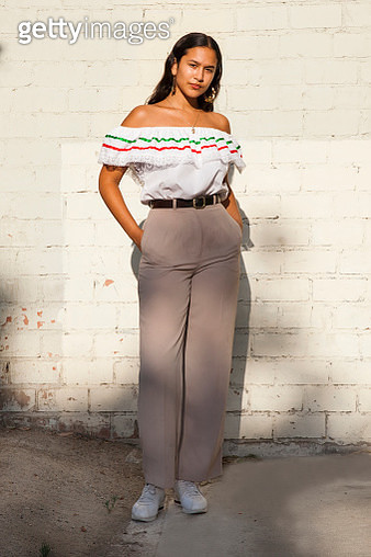 Young Latina woman wearing traditional fiesta ruffled top in front of white brick wall looking at camera - gettyimageskorea