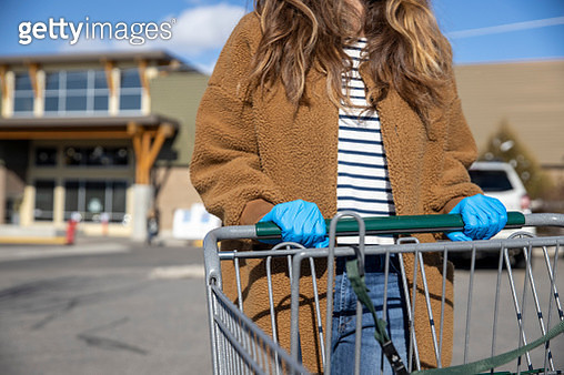A woman wearing blue latex gloves and pushing a shopping cart during the COVID-19 quarantine. - gettyimageskorea