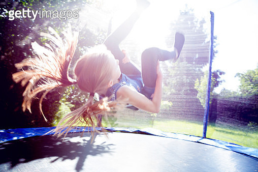 Girl (10-11) doing a somersault on a trampoline - gettyimageskorea