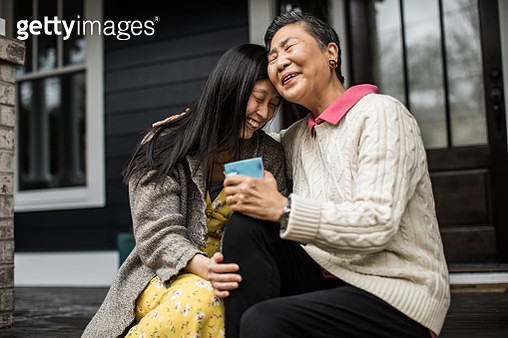 Adult woman and senior mother talking on front porch - gettyimageskorea