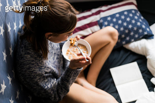 Top view of yung woman eating cereals and reading book - gettyimageskorea