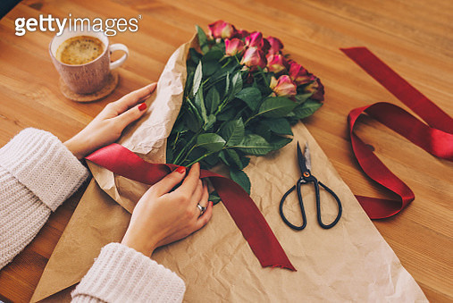 Woman making a bouquet of red roses - gettyimageskorea