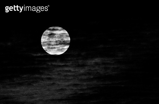 Stratified clouds across the full moon - gettyimageskorea