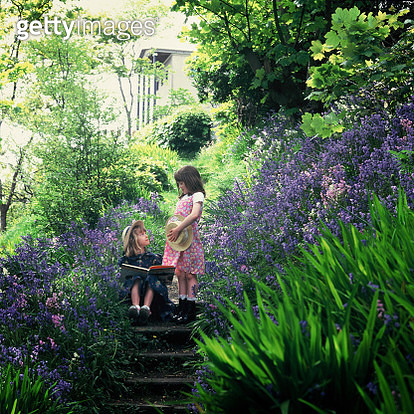 Two small children playing in a garden of Bluebell flowers - gettyimageskorea
