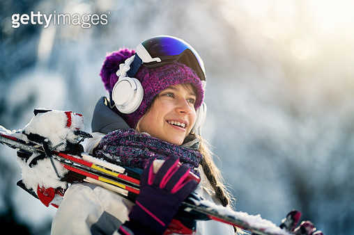 Teenage girl carrying skis on a winter day - gettyimageskorea