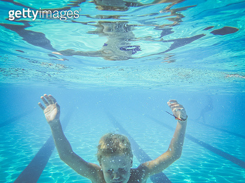 Boy Swims to the bottom of a pool - gettyimageskorea