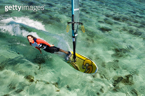 A man leans toward the water on his windsurf. - gettyimageskorea