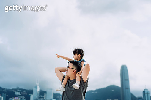 Young Asian father giving little daughter piggyback ride by the promenade of Victoria harbour, little girl pointing far away while looking over the beautiful city skyline - gettyimageskorea