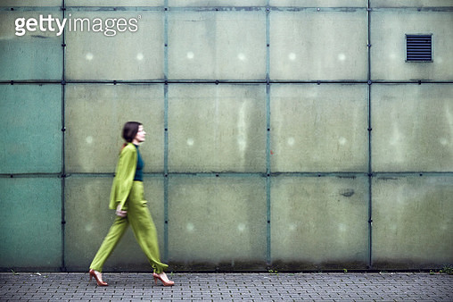 Businesswoman wearing green suit passing a wall - gettyimageskorea