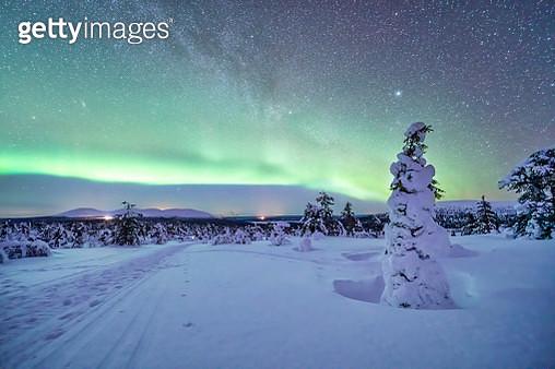 Northern lights over snow-covered landscape at dusk - gettyimageskorea