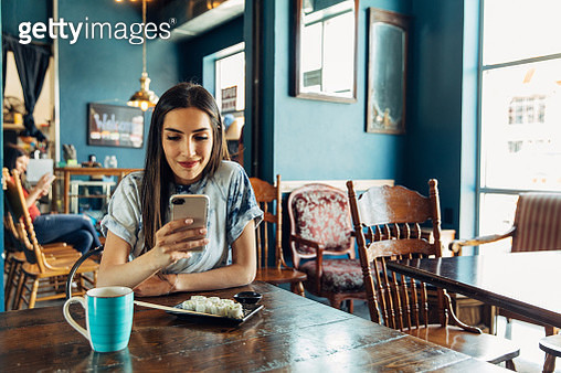 A Hispanic woman of the Millennial Generation is looking at her financial statement and showing a friend while eating lunch at a local sushi restaurant. She is using her bank's app to balance her monthly budget. Image taken in Utah, USA. - gettyimageskorea
