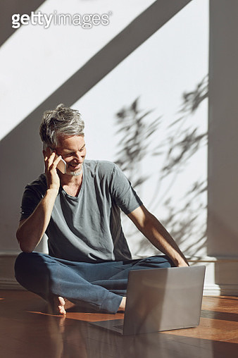 Mature man on the phone sitting on the floor at home with laptop - gettyimageskorea