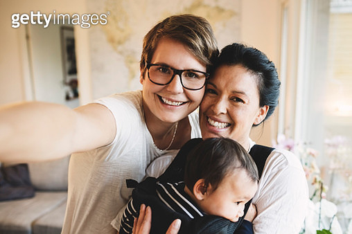 Portrait of smiling lesbian couple with baby girl standing at home - gettyimageskorea