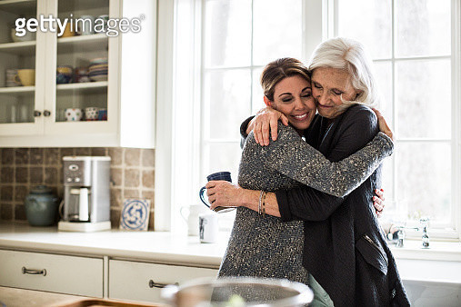 mother and daughter hugging in kitchen - gettyimageskorea
