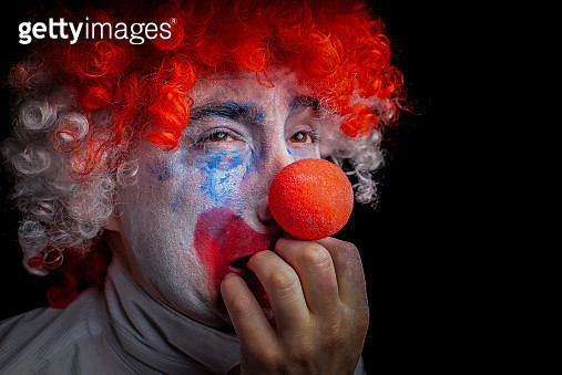 Close-Up Of Man In Clown Costume Biting Nails Against Black Background - gettyimageskorea