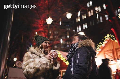 Young couple spending time eating on the street and enjoying Christmas decorations - gettyimageskorea
