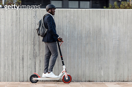 Smiling businessman on push scooter in front of concrete wall - gettyimageskorea