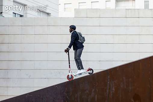 Businessman with backpack and cycling helmet on push scooter - gettyimageskorea