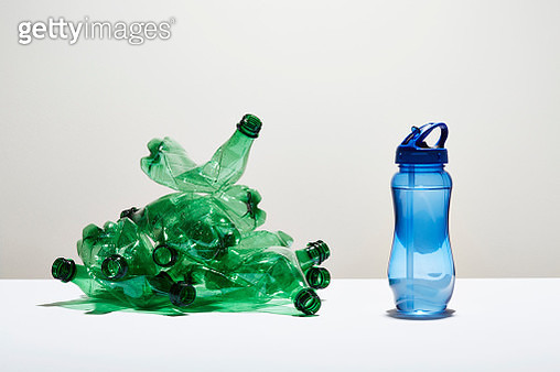 A heap of disposable water bottles next to a reusable water bottle - gettyimageskorea