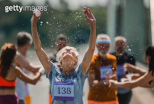 Senior woman running a marathon on the road and refreshing herself with water from a cup. There are people in the background. - gettyimageskorea