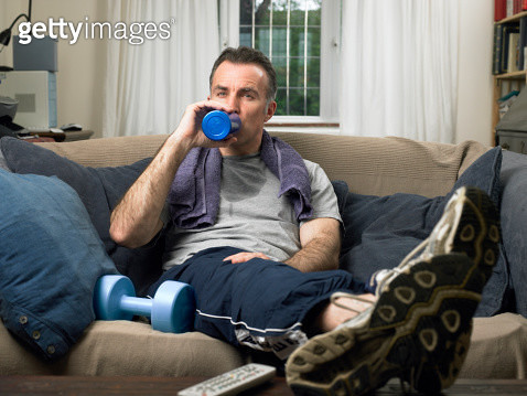 Man on sofa with feet up, towel around neck, drinking from bottle - gettyimageskorea