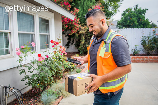 A young hispanic man delivering packages in a residential neighborhood. - gettyimageskorea