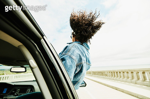 Rear view of woman leaning out of car window with hair blowing in wind - gettyimageskorea