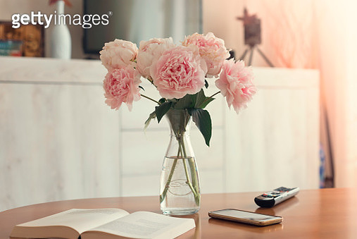 Vase of peonies,smartphone,book,and remote control on the Wooden living room table - gettyimageskorea