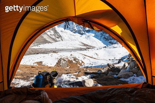 Looking out of tent to snowy mountains - gettyimageskorea
